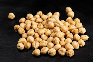 Roasted hazelnuts on a black background