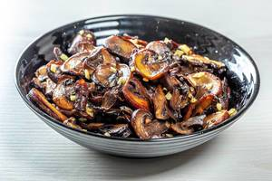 Roasted mushrooms with garlic on black bowl