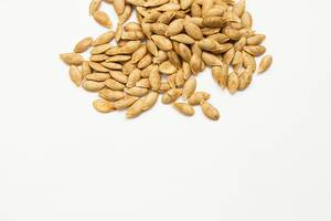 Roasted pumpkin seeds on white background