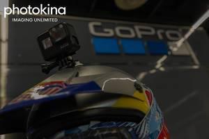 """Robuste Actionkamera von GoPro mit Helmhalterung auf einem RedBull-Rennfahrerhelm, neben dem Bildtitel """"photokina imaging umlimited"""""""