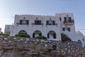 Rocks and wall in front of a Greek house with Mediterranean balconies, made of white limestone, on the Aegean island Paros