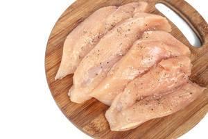 Rohe Hähnchenbrustfilets mit Kräutern auf einem hölzernen Küchenbrettchen