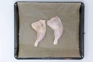 Rohe Hänchenkeulen auf Backblech mit Backpapier