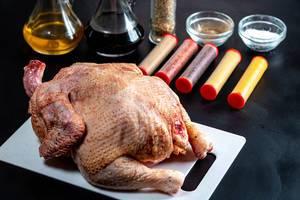 Rohe Hühnchen mit Zutaten zum Kochen, vor dunklem Hintergrund