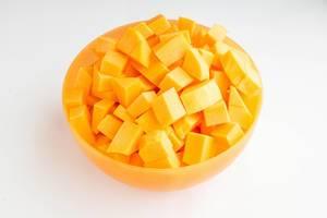 Rohe Kürbisstücke in einer orangenfarbigen Schüssel auf weißem Hintergrund