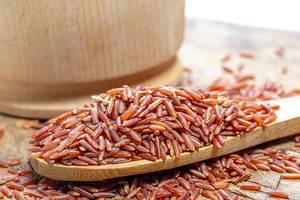 Roher brauner Reis auf einem Holzlöffel