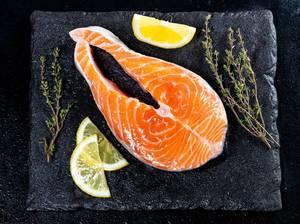 Rohes Lachsfilet mit Zitronenscheiben und Kräutern auf schwarzer Schieferplatte