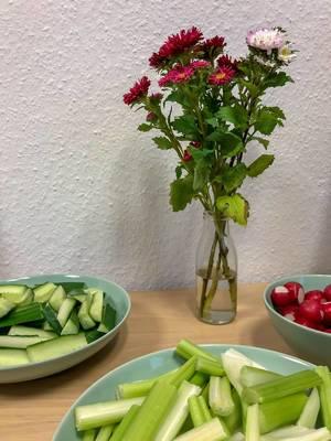 Rohkost - Gurken, Selleriestangen und Radischen in Schälchen mit einer Vase mit Blumen