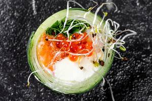 Roll with cucumber, salmon, cheese, arugula, micro greenery and red caviar on a black background. Top view (Flip 2019)