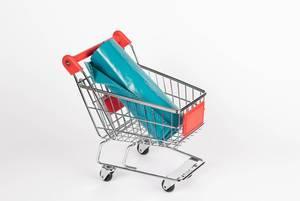 Rolle von Plastiktüten in Einkaufswagen vor weißem Hintergrund