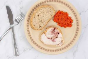 Rolled Chicken meat with homemade ajvar and bread on the plate