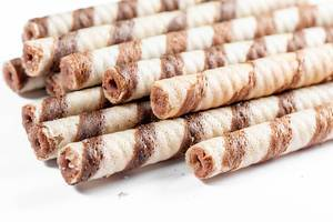 Rolled wafer filled with chocolate fudge on white background