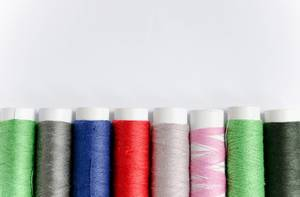 Rolled yarn of different colours on a white background
