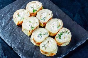 Rollen aus mit Käse und verschiedenen Kräutern gefüllten Eierpfannkuchen auf Schieferplatte