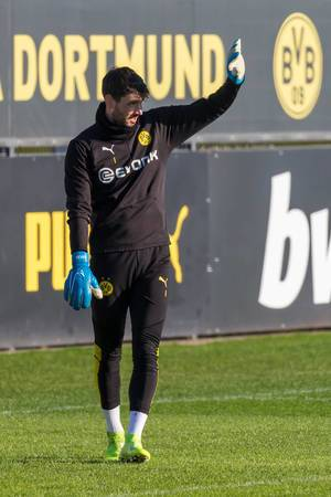 Roman Bürki uses his hand to protect his eyes as the winter sun shines during a training in Dortmund