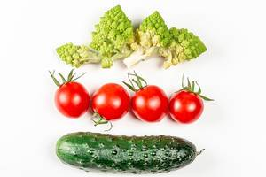 Romanesco, tomatoes and cucumber on a white background, top view (Flip 2020)