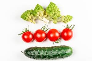Romanesco, tomatoes and cucumber on a white background, top view