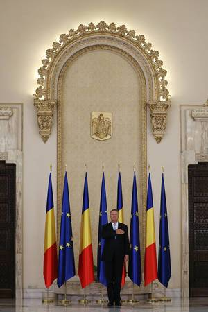 Romanian President Klaus Iohannis stands while listening the national anthem at Cotroceni Palace