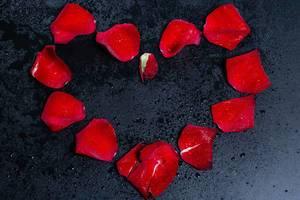Romantische Rosen-Blütenblätter in der Form eines Herzens auf schwarzem Hintergrund mit Wassertropfen