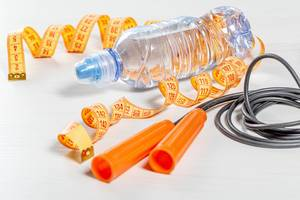 Rope, water bottle and measuring tape on white background. The concept of sports