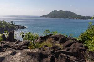 Ros Lepas schwarze Granitfelsen an der Klippe von Pointe Paul auf Mahé (Seychellen) mit Blick auf Cap Ternay im Indischen Ozean