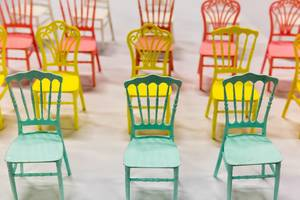 Rosa, gelbe und türkisfarbene winzige Stühle