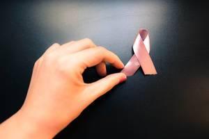 Rosa Schleife als Symbol gegen die Problematik von Brustkrebs mit der Hand einer Frau auf schwarzem Hintergrund