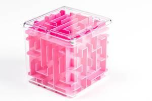 Rosa Spielzeug Labyrinth-Würfel mit einer kleinen Kugel vor weißem Hintergrund