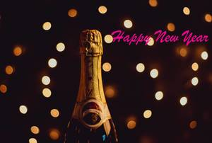 Rosaroter Text HAPPY NEW YEAR mit Champagner vor Bokeh Lichteffekten