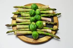 Rosenkohl mit grünem Spargel in Reihe auf runder Schieferplatte mit Holzrahmen