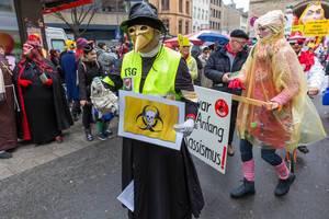 Rosenmontagszug in Köln gegen Rechts: Pappnasen rot-schwarz im Kostüm mit goldener Schnabelmaske, Antifaaufkleber und Totenkopf auf Biohazardlogo