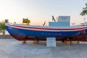 Rot-blau-weißes Fischerboot an Hafenpromenade in der Stadt Naoussa auf der griechischen Insel Paros