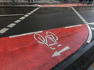 Rot markierter Fahrradweg führt von einer Straßenseite zur anderen
