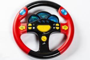 Rot-schwarzes Spielzeug-Lenkrad mit Tacho und Messgeräten auf weißem Hintergrund