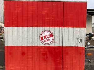 Rot-weiß bemalte Wand mit Aufkleber des Fußballvereins 1. FC Köln mit Fahrrad im Hintergrund