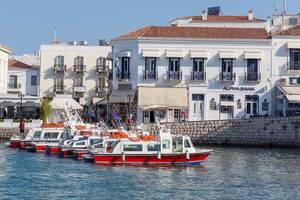 Rot-weiße Wassertaxis als Wassertransportmittel, vor einer griechischen Hafenstadt