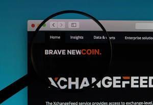 """Rot-weißer """"Brave New Coin"""" Schriftzug unter einer Lupe"""