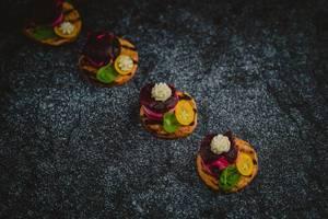 Rote Beete Appetithappen mit Basilikum und einem Stück Zitrusfrucht - diagonale Nahaufnahme