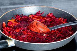 Rote Beete mit Karotten und Zwiebeln in einer Pfanne gebraten und mit Tomatenmark auf einem Kochlöffel
