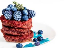 Rote Bete Pfannkuchen mit Maulbeeren und frischen Blaubeeren, auf einem weißen Teller