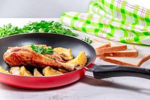 Rote Bratpfanne mit gekochtem Essen
