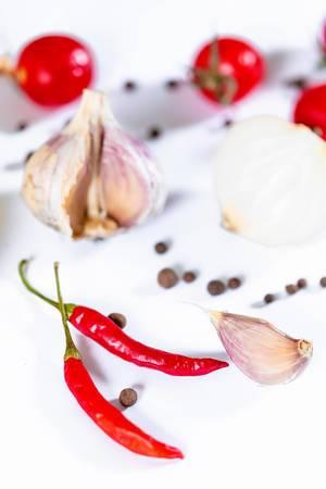 Rote Chilischoten, Cherrytomaten, Knoblauch und schwarze Pfefferkörner auf weißem Hintergrund