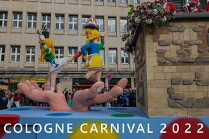 "Rote Funken carnival wagon shows dancing girls in costumes on gigantic hands, during rose Monday procession & picture title ""Cologne Carnival 2022"""