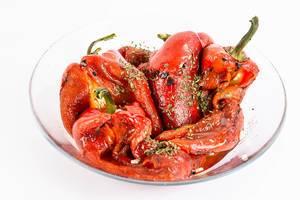 Rote gegrillte Paprika mit Kräutern in einer Glasschale