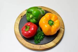 Rote, grüne und gelbe Paprika mit krauser Petersilie auf runder Schieferplatte mit Holzrahmen
