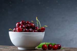 Rote Kirschen an Strängen, in einer weißen Schale, auf einem Holztisch