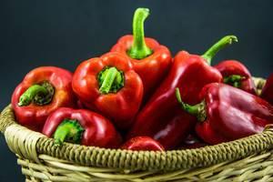 Rote Paprika in Obstkorb vor dunklem Hintergrund