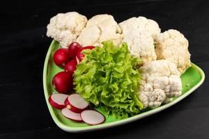 Rote Radieschen, Blumenkohl und grüner Salat auf dreieckigem Teller auf schwarzem Untergrund