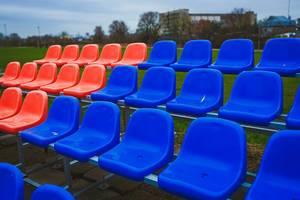 Rote und blaue Stadionsitzreihen auf einer Wiese