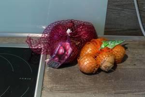 Rote und weiße Zwiebeln in Netz auf Küchenablage neben Herdplatte